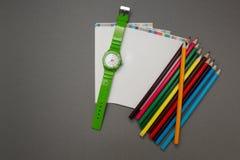 Wristwatch, notatnik i ołówek na szarym tle, obraz royalty free