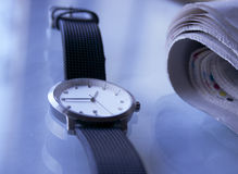 Wristwatch and paper. A modern wristwatch and newspaper lying on a tabletop stock image