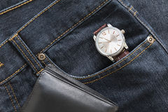 Wristwatch and wallet on denim jeans pocket Stock Photo