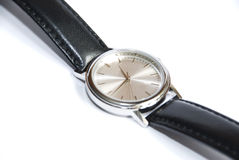 Wristwatch on white. Wrist watch made of white metal, with black leather strap on a white background royalty free stock images