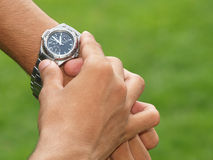 Wristwatch on wrist. Man displaying wristwatch on wrist (body and face not visible. Checking the time Royalty Free Stock Image
