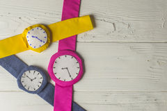 Wristwatches. Three Rag Multi Colored Wristwathes on Wooden Background Royalty Free Stock Photos