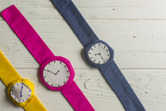 Wristwatches. Three Rag Wristwatches in Row on Wooden Background Royalty Free Stock Images