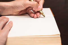 Write on book. Hand holding pencil write on open book Royalty Free Stock Photos