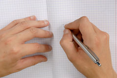 Write it down. There are hands which try to wright something on graph paper royalty free stock photos