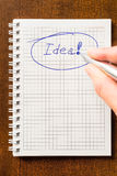 Write down an idea to notebook. Lying on the wooden table Royalty Free Stock Photo