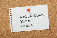 Write Down Your Goals. Typed on a scrap of paper pinned to a cork notice board. Writing down goals helps to make them more real and will provide focus as you royalty free stock photography