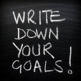 Write Down Your Goals!. The words Write Down Your Goals written by and in white chalk on a blackboard as a reminder. A vignette has been added fro effect royalty free stock photography