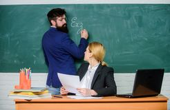 Write down your task. Check homework. Teachers working in pairs school classroom. School educator and teacher trainee. With documents. Educational program stock images