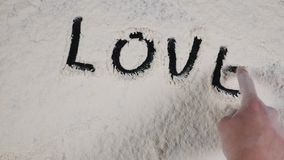 Write a finger LOVE on a white flour background. top view 4k.  stock video footage