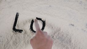Write a finger LOVE on a white flour background. top view 4k.  stock footage
