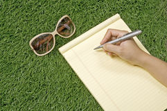 Write On The Grass. People writing on the paper over green grass. You can write your message on the paper stock images