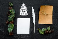 Write greetings. Envelope, paper, pen and hello winter hand lettering on black background top view pattern. Write greetings. Envelope, paper, pen and hello Royalty Free Stock Photos