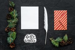 Write greetings. Envelope, paper, pen and hello winter hand lettering on black background top view pattern. Write greetings. Envelope, paper, pen and hello Stock Image