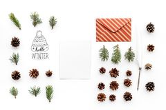 Write greetings. Envelope, paper, spruce branches and cones and hello winter hand lettering on white background top view Royalty Free Stock Images