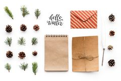Write greetings. Envelope, paper, spruce branches and cones and hello winter hand lettering on white background top view Stock Images