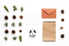 Write greetings. Envelope, paper, spruce branches and cones and winter hand lettering on white background top view Royalty Free Stock Photography