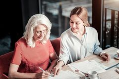 Cheerful smiling woman pointing to the space for a signature. Write here. Kind attentive young women sitting at the table and helping her older colleague while Stock Image
