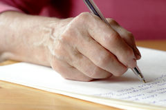 Write a letter.    pen in the hands of an elderly woman and Paper Royalty Free Stock Image