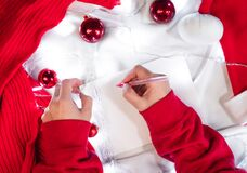 Write a letter with wishes on a white blanket. Write a wish list for Santa with a red pen on a blank white sheet. Red Christmas