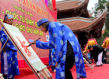 Write letters in the new year. HAI DUONG, VIETNAM, February, 15: the teacher in traditional costumes to write letters in the new year for good luck at Chu Van An Royalty Free Stock Photos