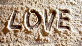 Write love on flour closeup stock video