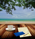 Write mail with hot coffee beside the sea Stock Photography