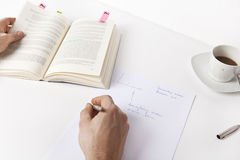 Write notes from a book. Only the hands are seen, no face Royalty Free Stock Photo