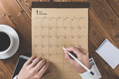 Write a schedule to a calendar placed on a wooden table Royalty Free Stock Images