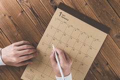 Write a schedule to a calendar placed on a wooden table Royalty Free Stock Image
