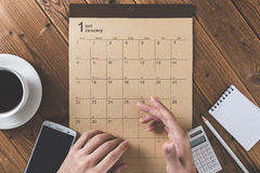 Write a schedule to a calendar placed on a wooden table Royalty Free Stock Photo