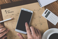 Write a schedule to a calendar placed on a wooden table Stock Image