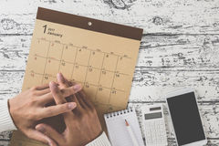 Write a schedule to a calendar placed on a wooden table Stock Photo