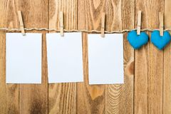 Write some words of love. Blank sheet of paper hand made heart pinned to rope on wooden background Stock Photography