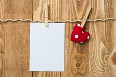 Write some words of love. Blank sheet of paper hand made heart pinned to rope on wooden background Stock Images
