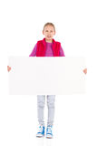 Write something on my placard. Little girl standing and holding blank banner. Full length studio shot isolated on white Royalty Free Stock Images