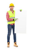 Write something on this white board. Manual worker in yellow helmet and reflective waistcoat holding white placard and pointing. Full length studio shot isolated Royalty Free Stock Image