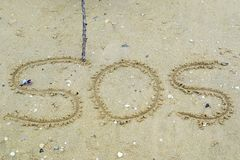 Write a symbol for help on the sand. SOS symbol on the sand Stock Photo