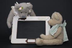 Write with teddy bear. A couple of teddy bear near a blackboard where you can write anything Stock Photos