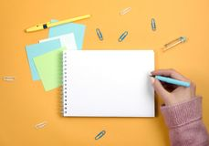 Write thoughts and ideas in a clean white notebook on an orange background royalty free stock photography