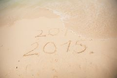 2014 and 2015 write on white sand Stock Images