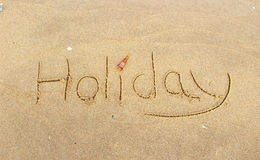 Write word holiday on sand beach Royalty Free Stock Photo
