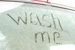 Write the words wash me on the very dirty surface of the car. Concept car wash