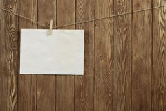 Write your message. Blank sheet of paper hanging on rope Stock Image