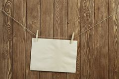 Write your message. Blank sheet of paper hanging on rope Royalty Free Stock Photo