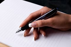 Writer. Female hand holding a pen Royalty Free Stock Images