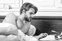 Writer author used old fashioned machine instead of digital gadget. Morning inspiration. Writer use manual typewriter. Daily work. Man writer lay bed working on stock images