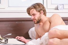 Writer author used old fashioned machine instead of digital gadget. Morning inspiration. Writer use manual typewriter. Daily work. Man writer lay bed working on royalty free stock photo