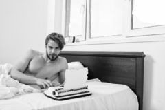 Writer author used to old fashioned machine instead of digital gadget. Man writer lay on bed white bedclothes working on. New book. Morning inspiration concept stock photos