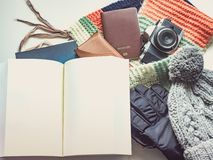 Writer with book in holiday and winter season travel flat lay co. Ncept from  winter cloth item and passport, sunglasses with copy space and isolated white Royalty Free Stock Photos